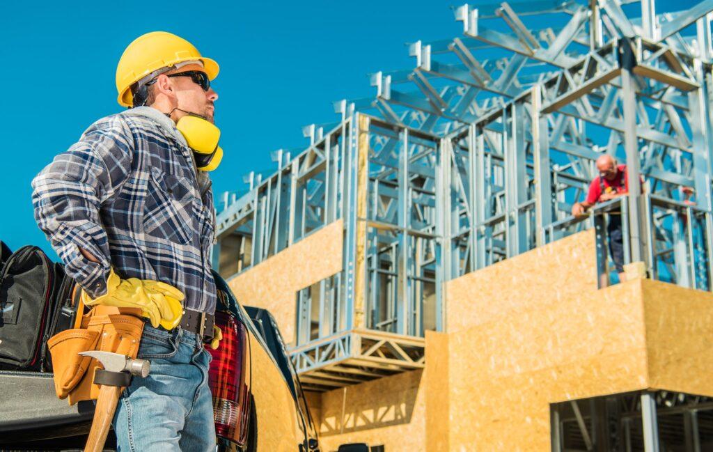 travailleur de chantier devant un bâtiment en construction