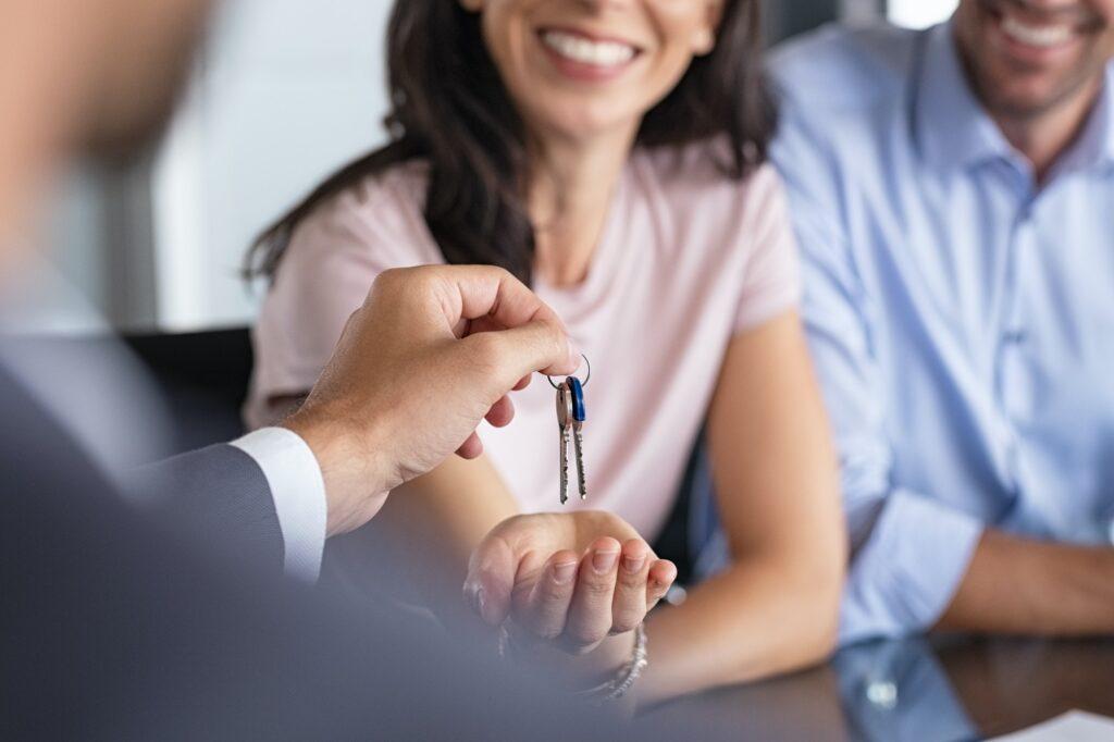 agent immobilier donne les clés d'une maison à ses clients