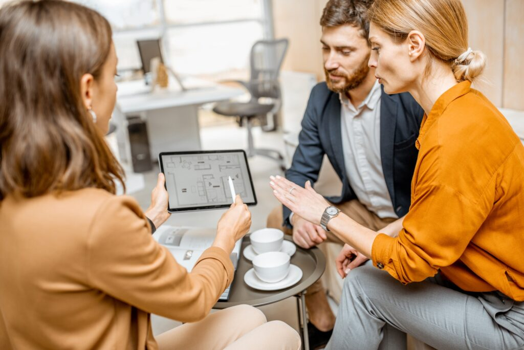 promoteur immobilier montre les plans d'une maison à ses clients