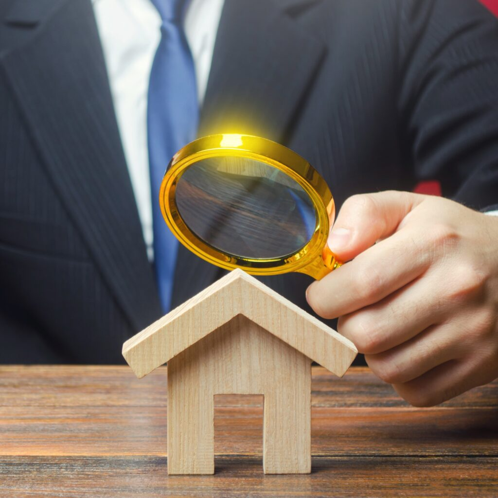 Man in a suit looking at a miniature house through a magnifying glass. House inspection concept